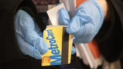A woman wears protective gloves as she poses with a metro card at a subway station