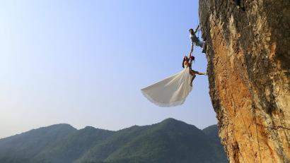 An amateur climber takes wedding pictures with his bride on a cliff