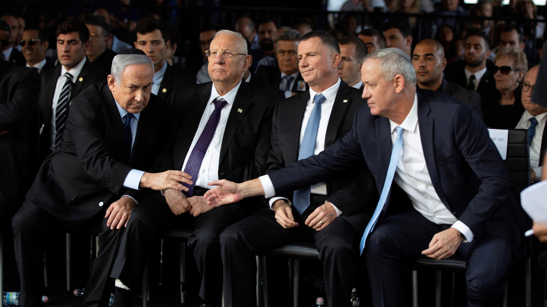 Netanyahu and Gantz reach out to shake hands.