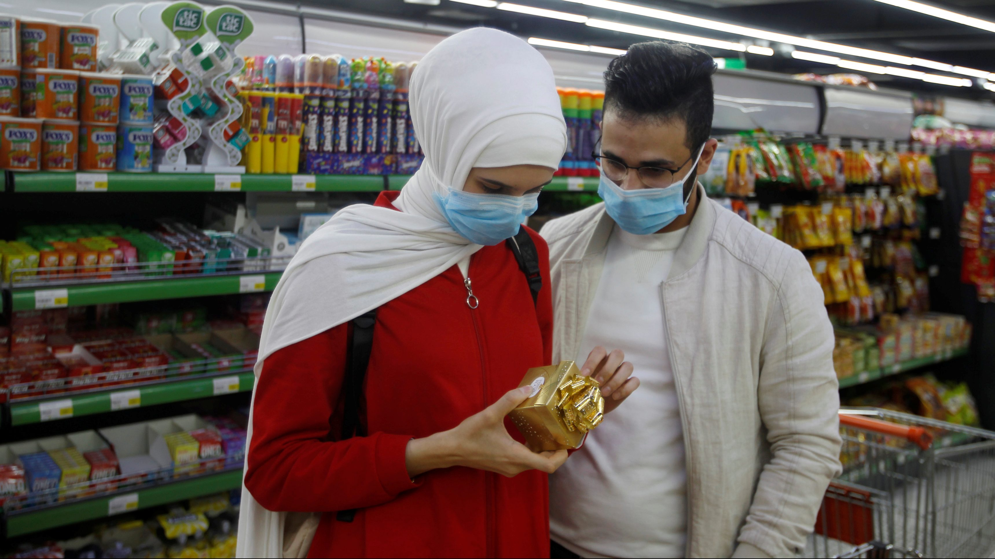 A man and his wife wear protective face masks at a supermarket