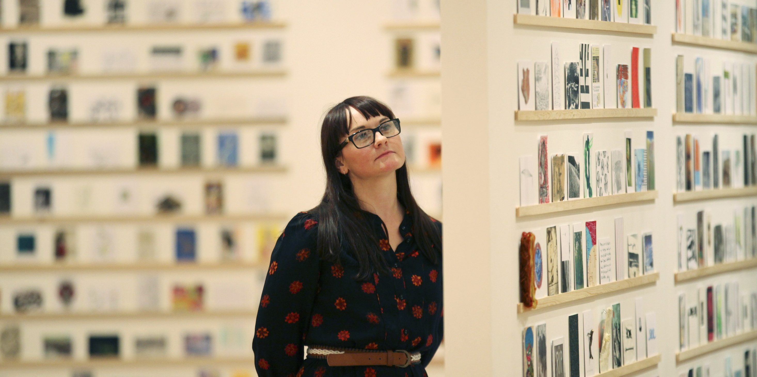 An art student poses for photographers at the annual Royal College of Art Secret Postcards exhibition which goes on display ahead of next week's sale in London