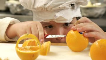 Zeke Andreassen, 11, cuts an orange into a decorative basket in the kitchen of the Vermont Kids Culinary Academy during a residential cooking summer camp in Highgate