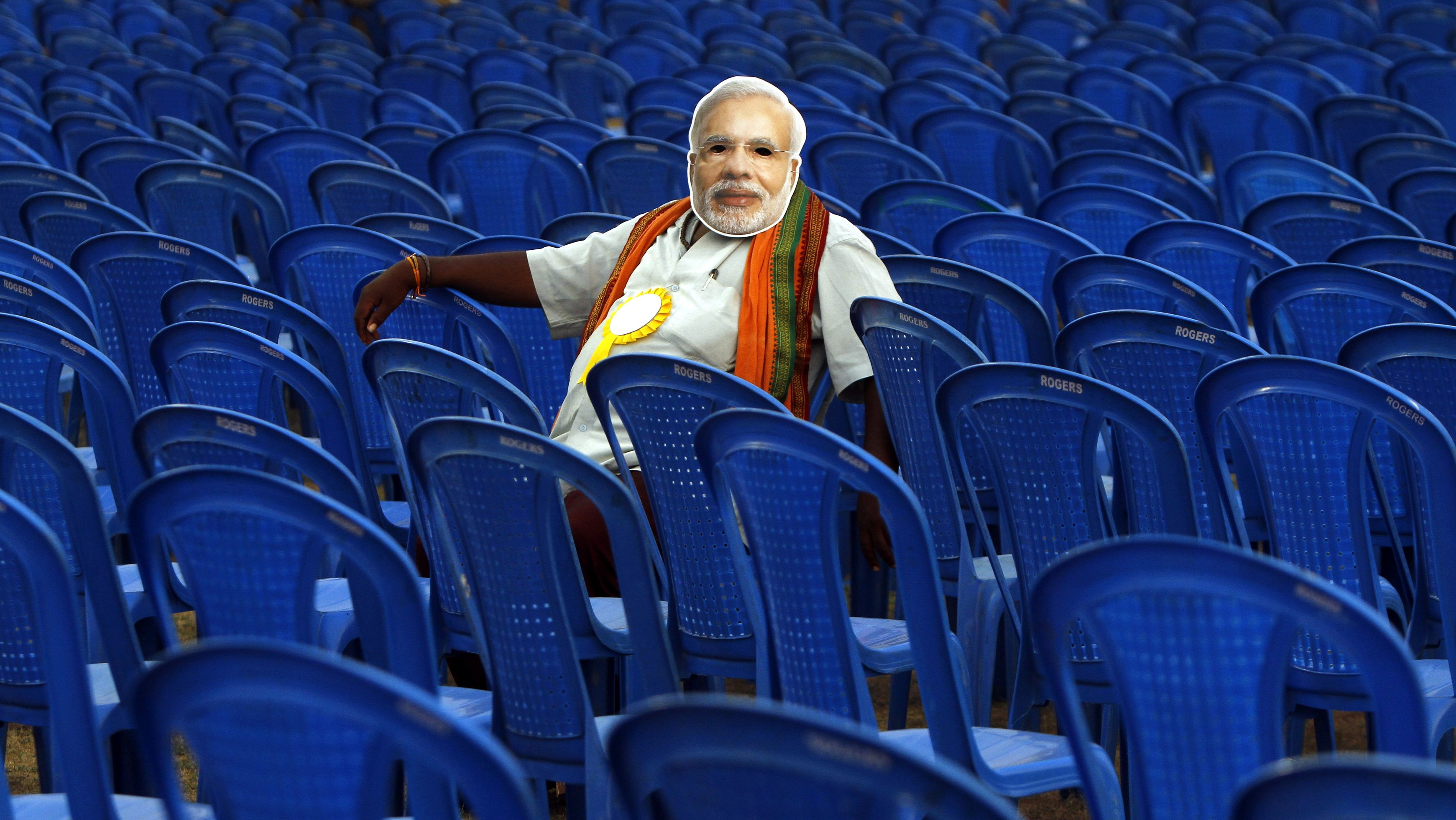 A supporter of Modi, prime ministerial candidate for BJP, wears a mask depicting Modi as he sits before the start of an election campaign rally in the southern Indian city of Chennai