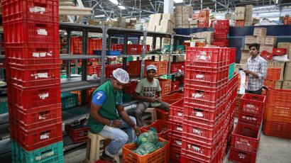 Employees sort out orders before sending them out at a Big Basket warehouse on the outskirts of Mumbai