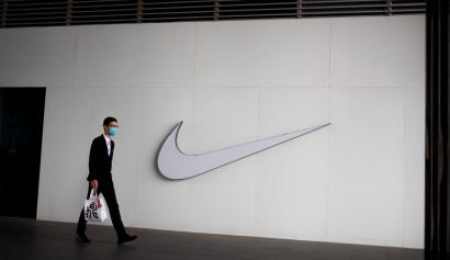 A man wearing a face mask passes a Nike store, as the country is hit by the novel coronavirus outbreak, in Beijing