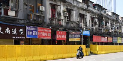 Man wearing a face mask rides a bike past shops blocked by barricades in Wuhan, the epicentre of the novel coronavirus outbreak