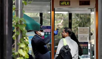A private security guard uses an infrared thermometer to measure the temperature of a man at the entrance of an office building, following an outbreak of the coronavirus disease, in New Delhi