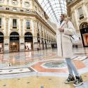 A woman wearing a protective face mask takes a selfie in Galleria Vittorio Emanuele II shopping mall