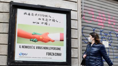 A woman, wearing a protective face mask, walks past a placard showing a handshake between two hands representing the Chinese and the Italian national flags