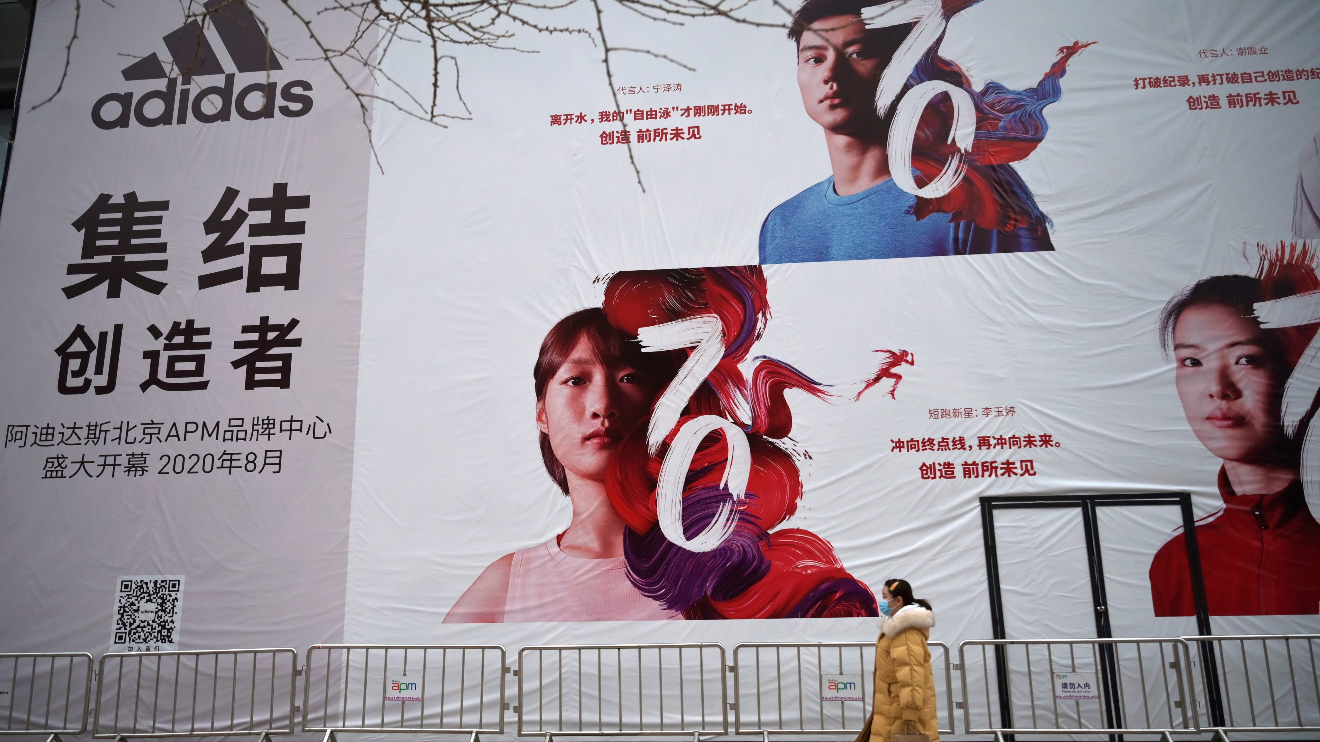 A woman wearing a face mask walks past a banner advertising new Adidas store in Beijing