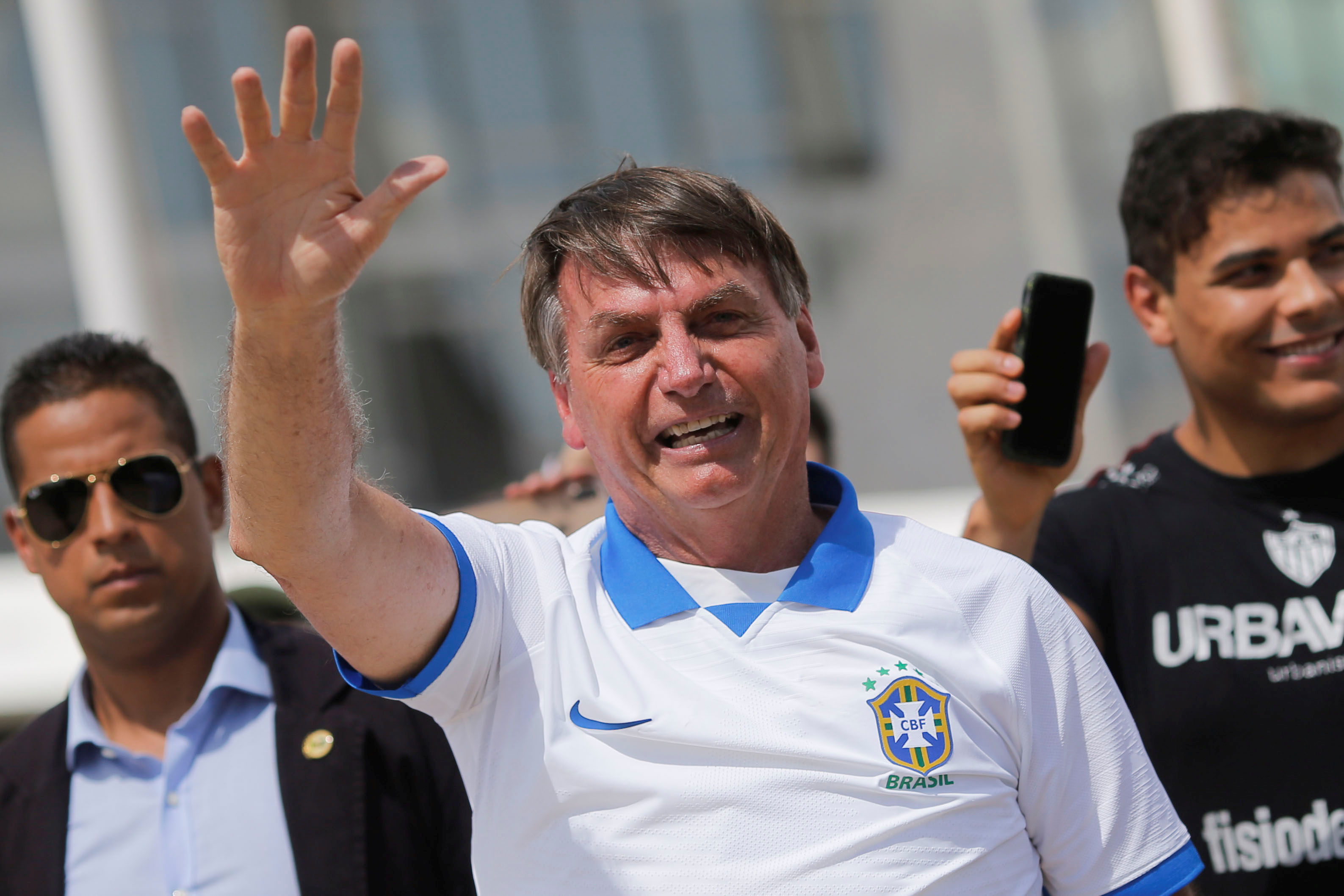 Brazilian president Jair Bolsonaro, who has been criticized for not taking the coronavirus seriously, waves at a crowd while wearing a soccer shirt.