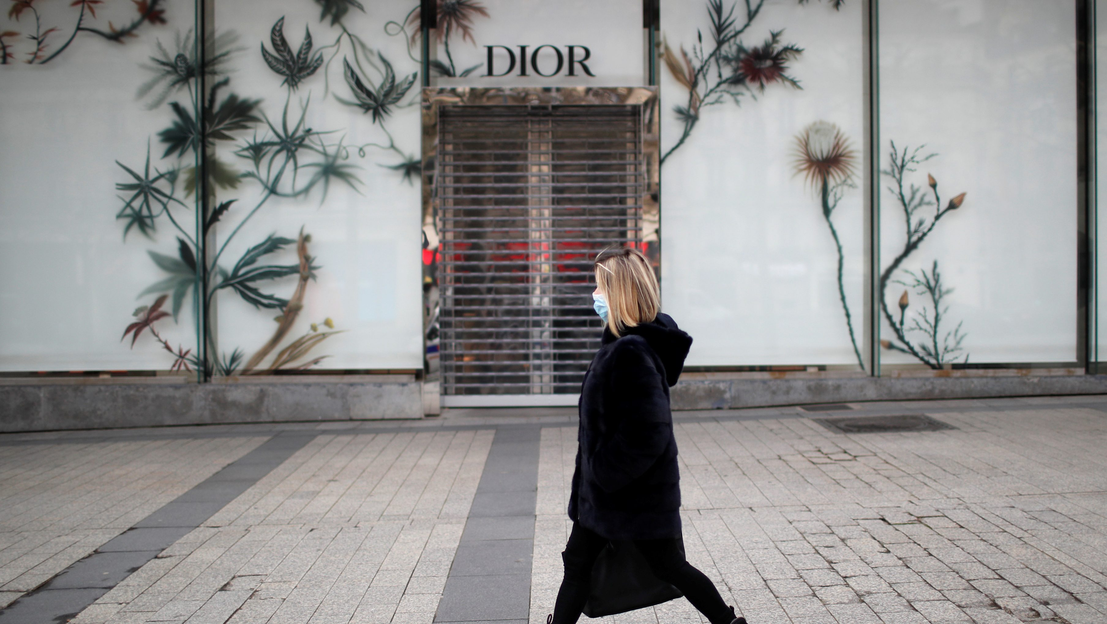 A woman wearing a protective face mask walks past the closed Dior shop on the Champs Elysees Avenue in Paris