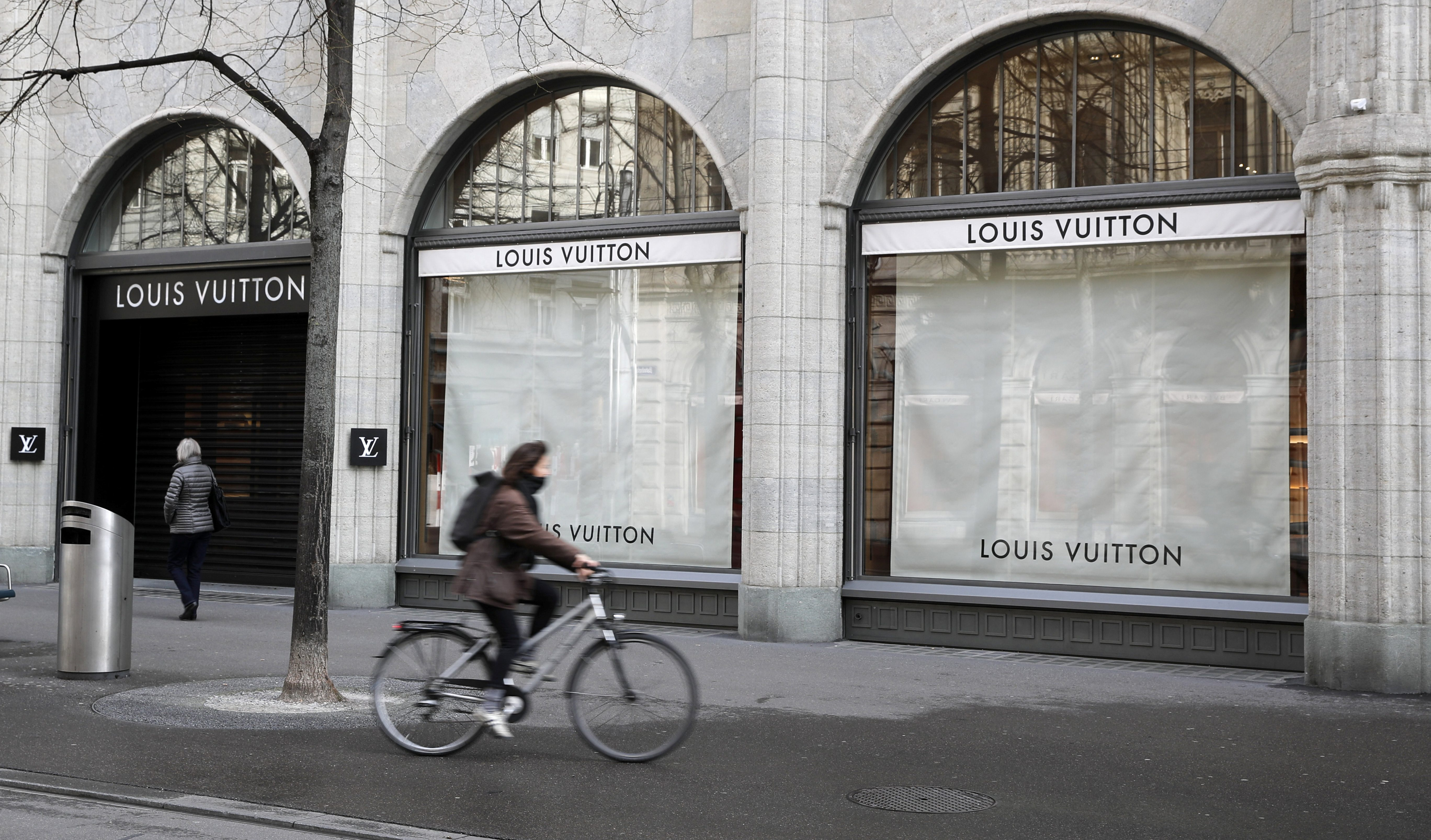 A woman cycles past a closed shop French luxury company Louis Vuitton at the Bahnhofstrasse shopping street in Zurich