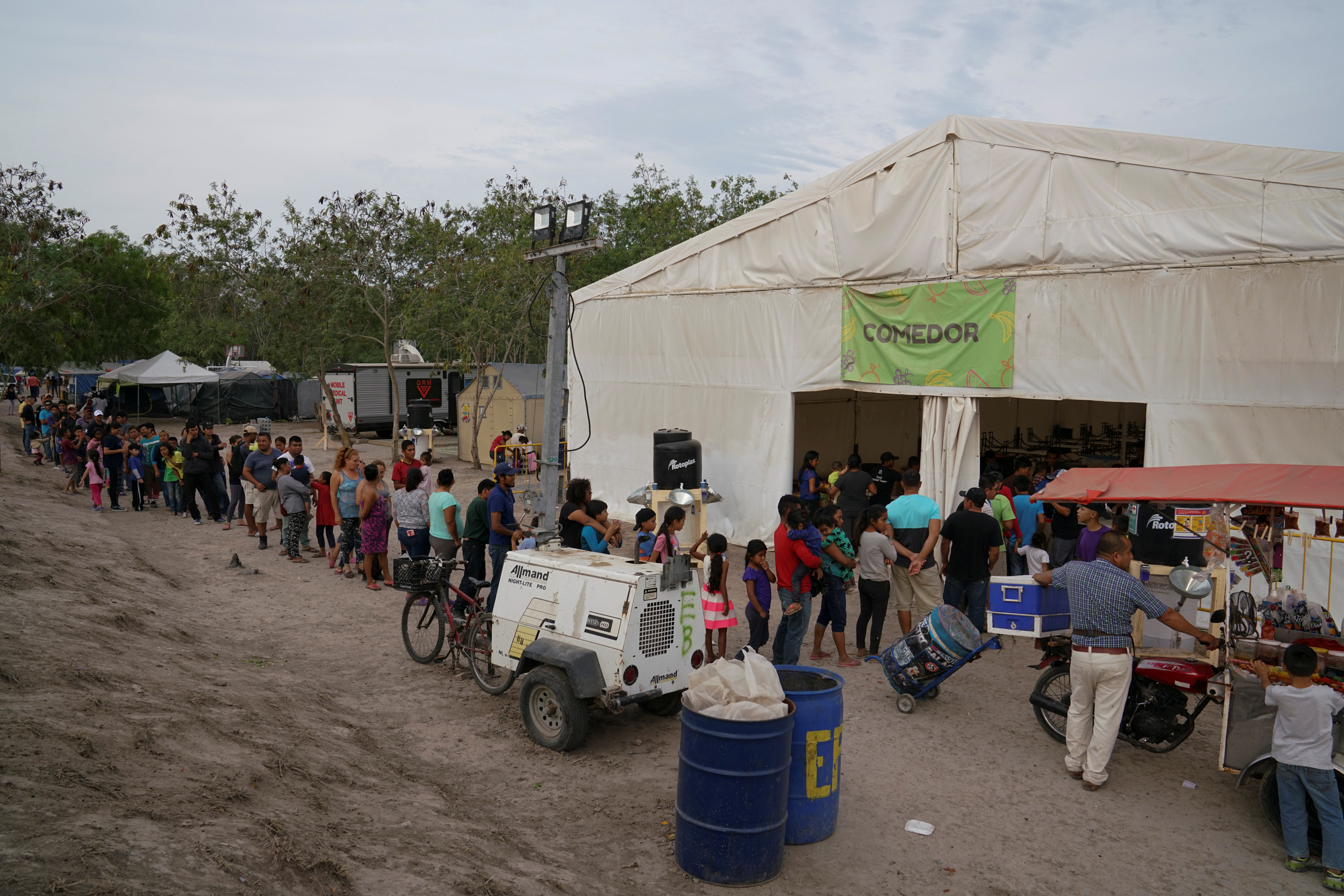 People wait in line for a meal at the Matamoros migrant encampment.