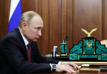 Putin stares from a seat in a gilded office.