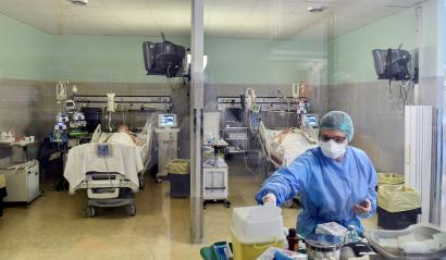 A medical worker wearing a protective mask and suit treats patients suffering from coronavirus disease (COVID-19) in an intensive care unit at the Oglio Po hospital in Cremona, Italy