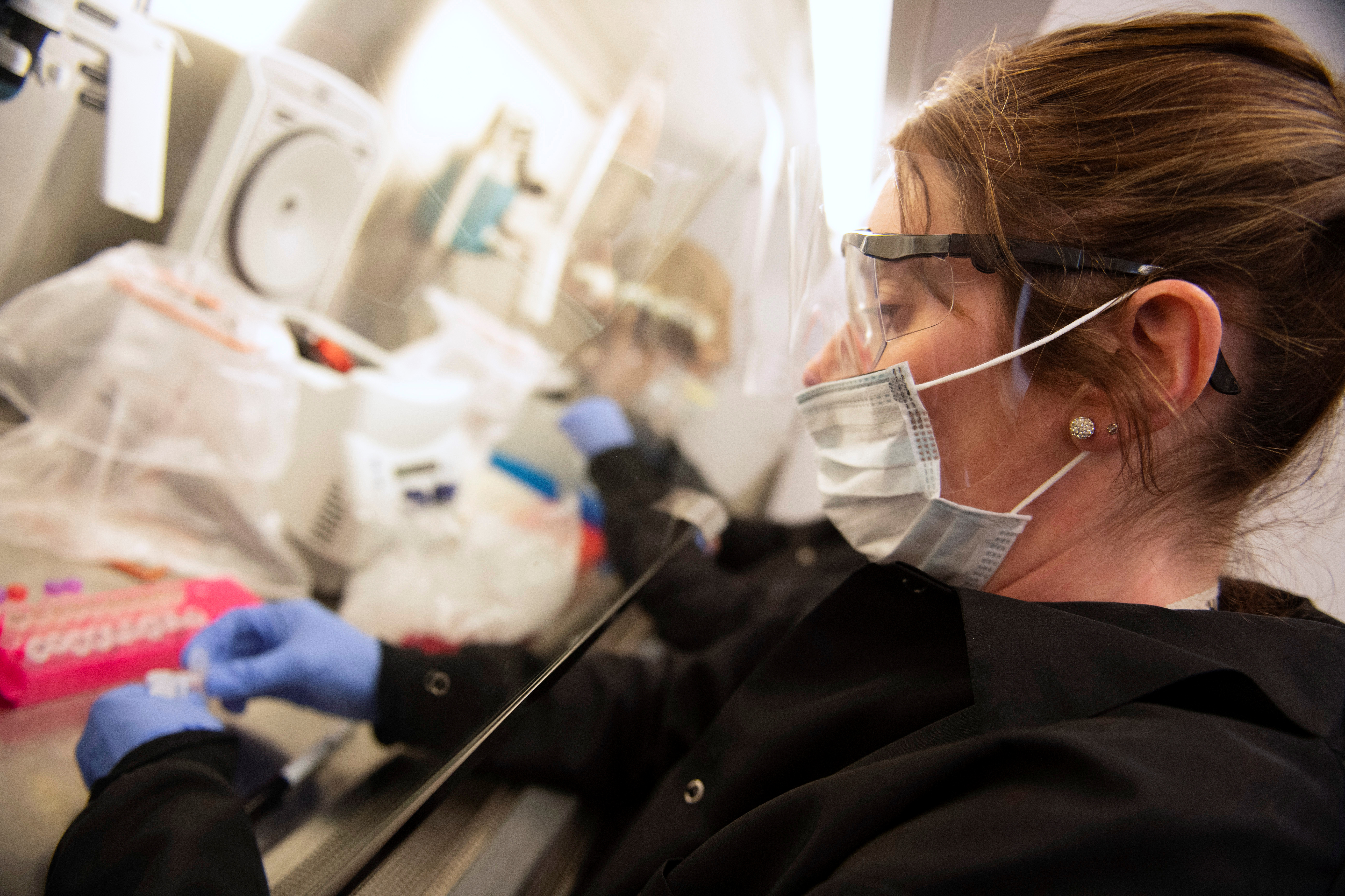 Kylene Karnuth, a clinical lab scientist, works with coronavirus samples as researchers begin a trial to see whether malaria treatment hydroxychloroquine can prevent or reduce the severity of the coronavirus disease.