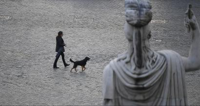 A woman walks her dog in Rome.