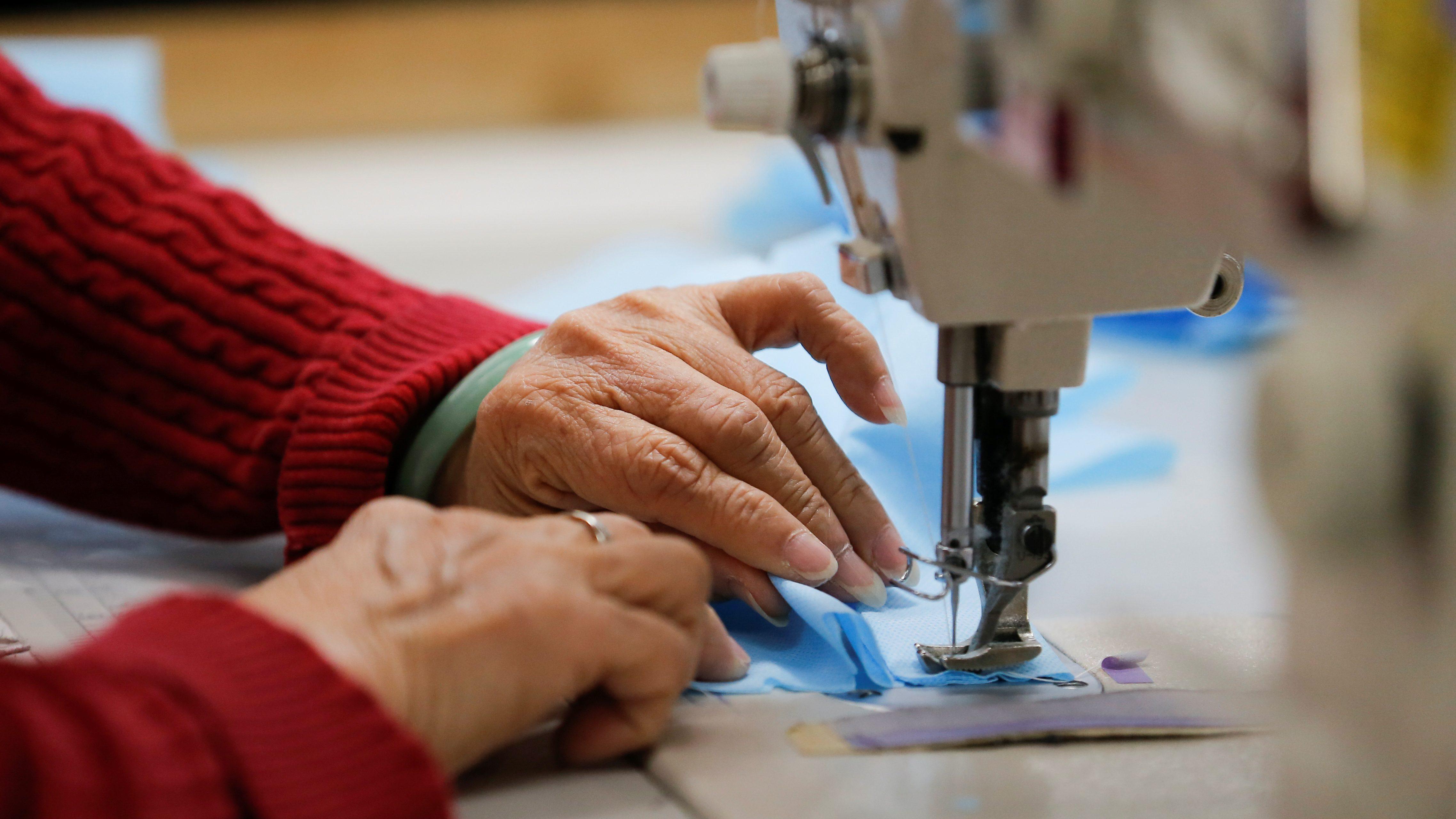 An employee sews masks at a clothing manufacturer