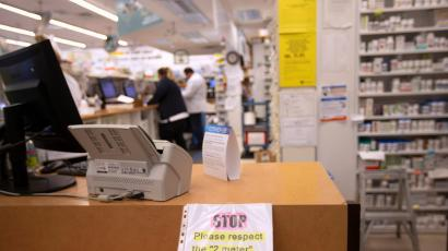 The counter in a pharmacy line. Drugs are visible on the right hand side, and a sign by the register reminds patients to wait six feet behind each other.