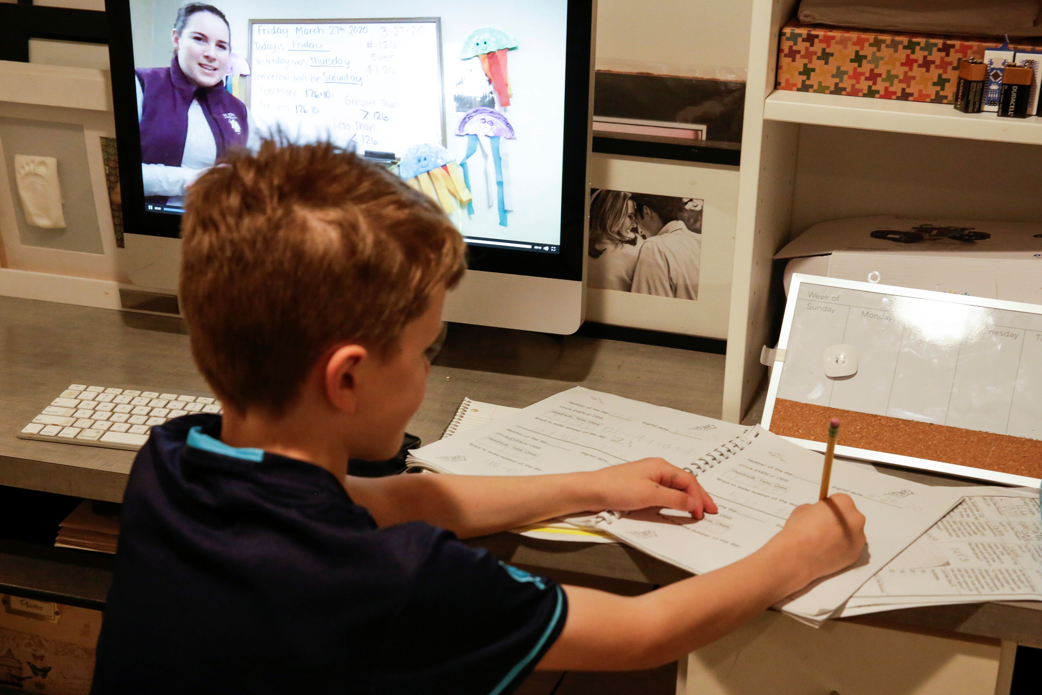 Oakes McClenahan, 7, does his school work as he watches his teacher's recorded lesson on a computer in Washington.