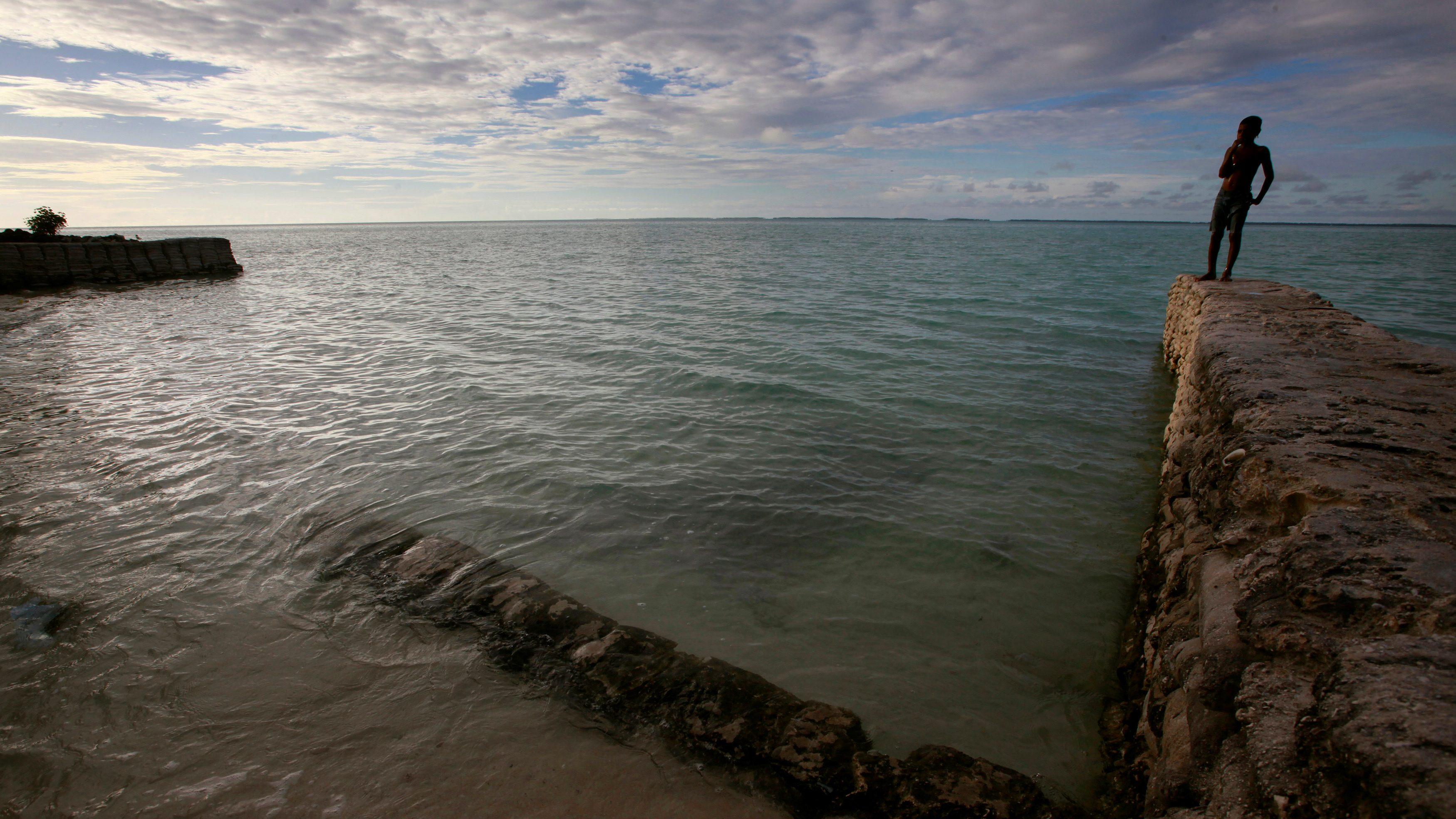 Boy seawall Kiribati