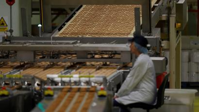 A worker inspects biscuits on the production line of Pladis' McVities factory in London