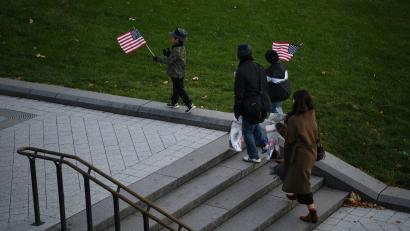 Children hold American flags while walking near the U.S. Capitol building on Capitol Hill in Washington