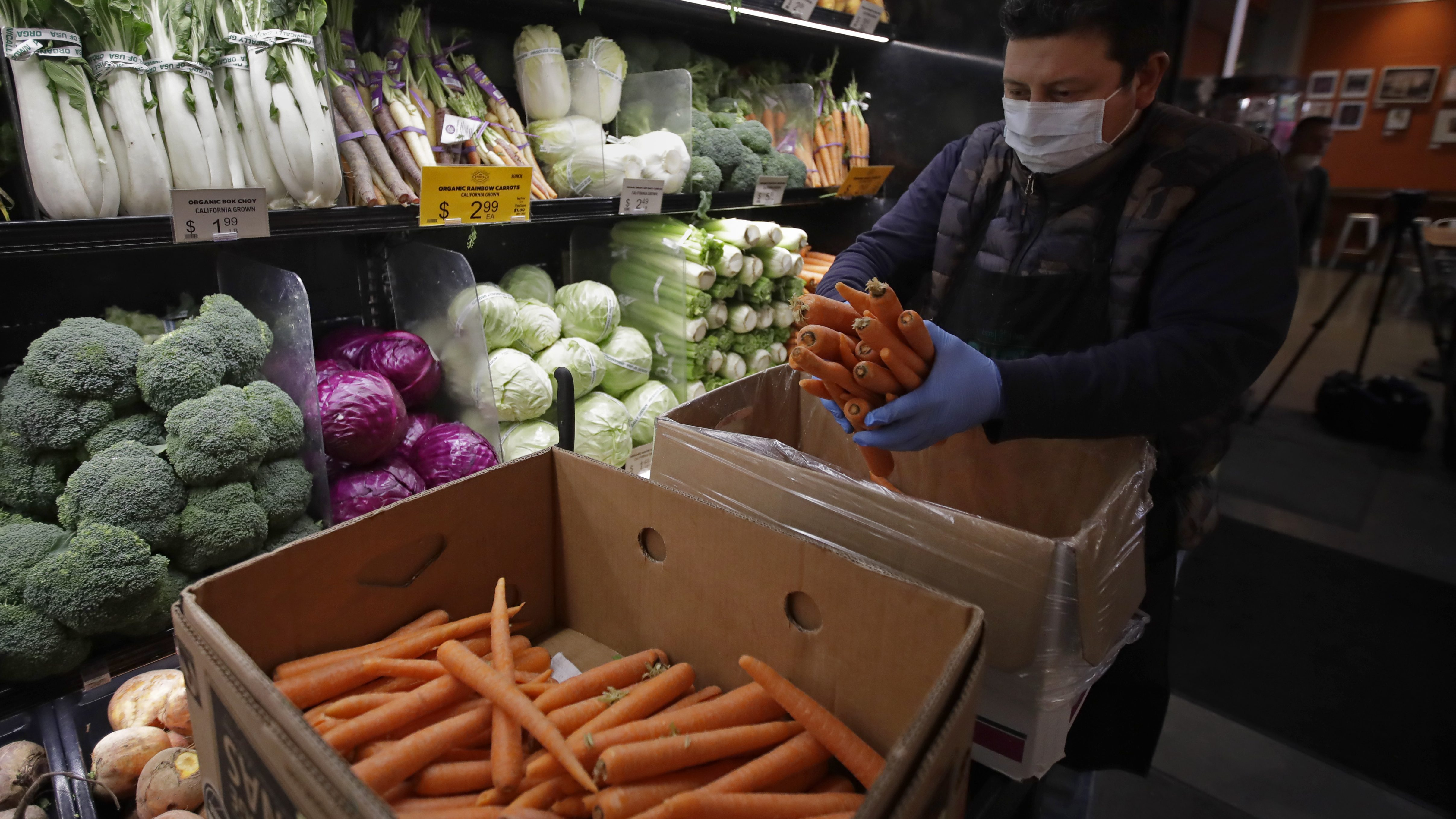 A worker, wearing a protective mask against the coronavirus, stocks produce.