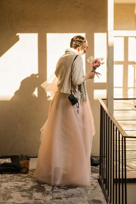 A photo of Christie heading out of their apartment in her wedding dress, bouquet in hand.