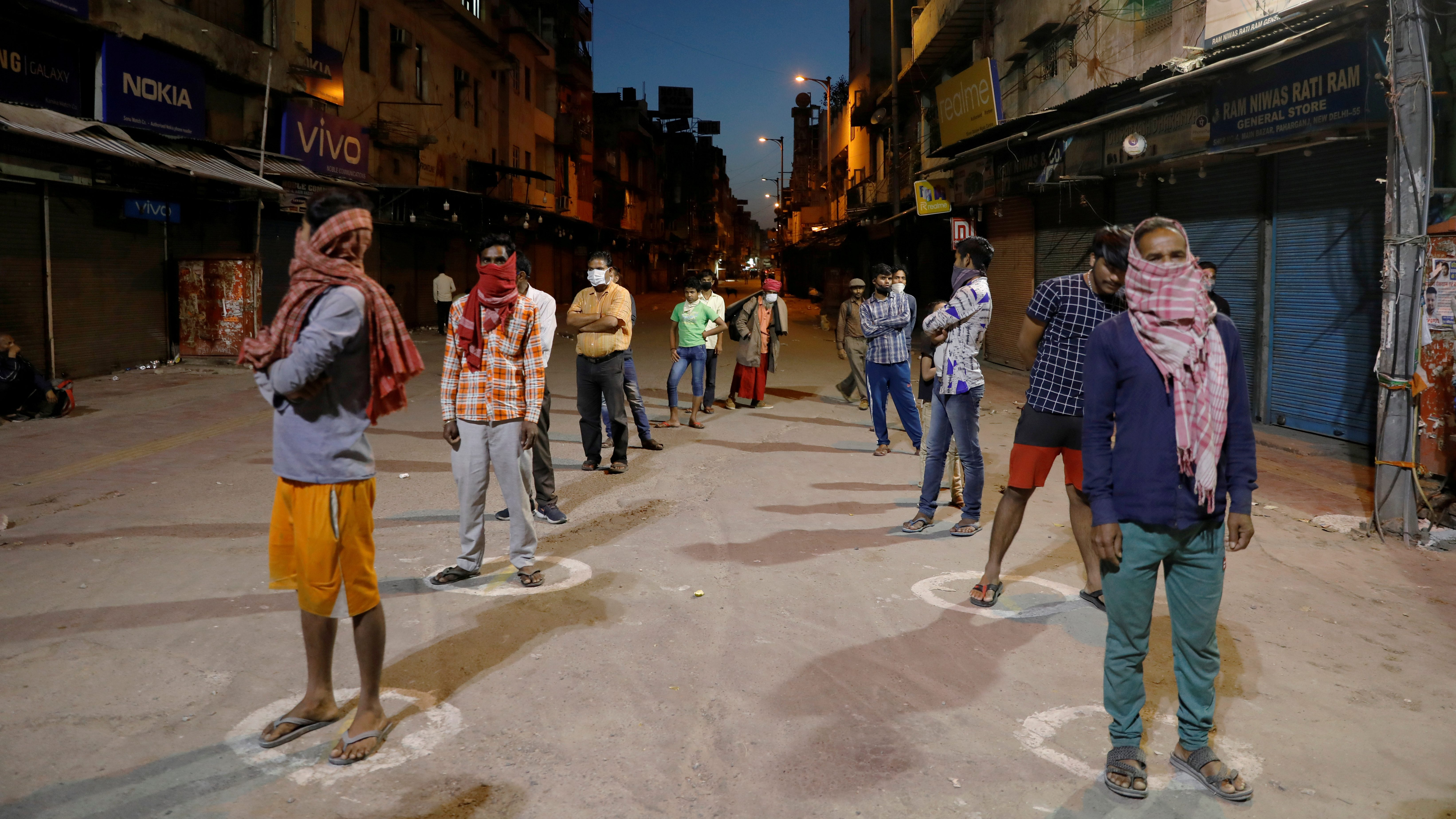 People stand apart in a line to receive free food being distributed on a street in New Delhi.