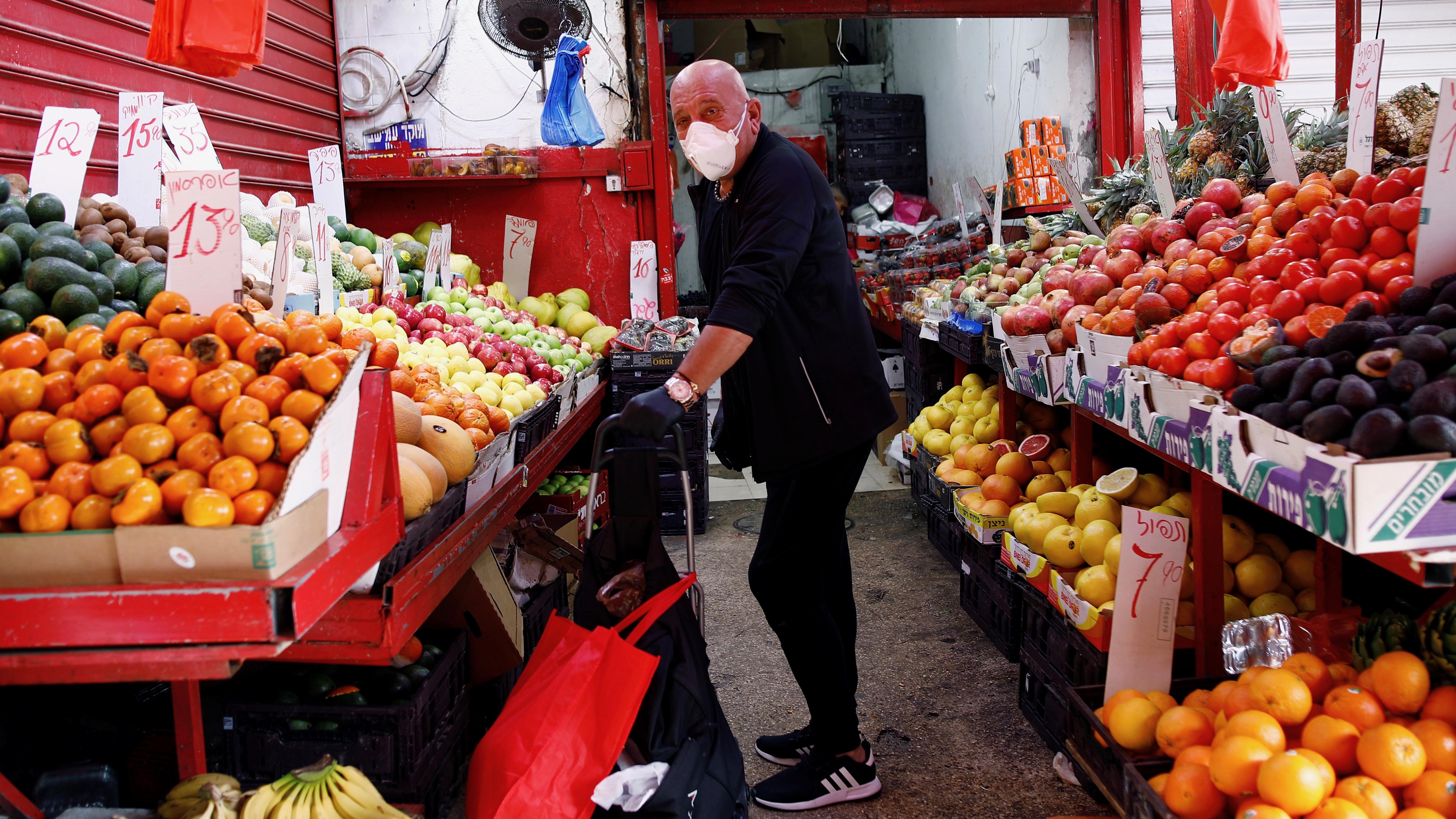 A masked man shops in Tel Aviv.