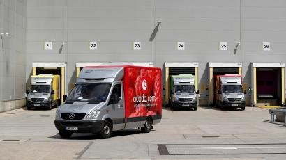 An Ocado delivery truck leaves a warehouse.