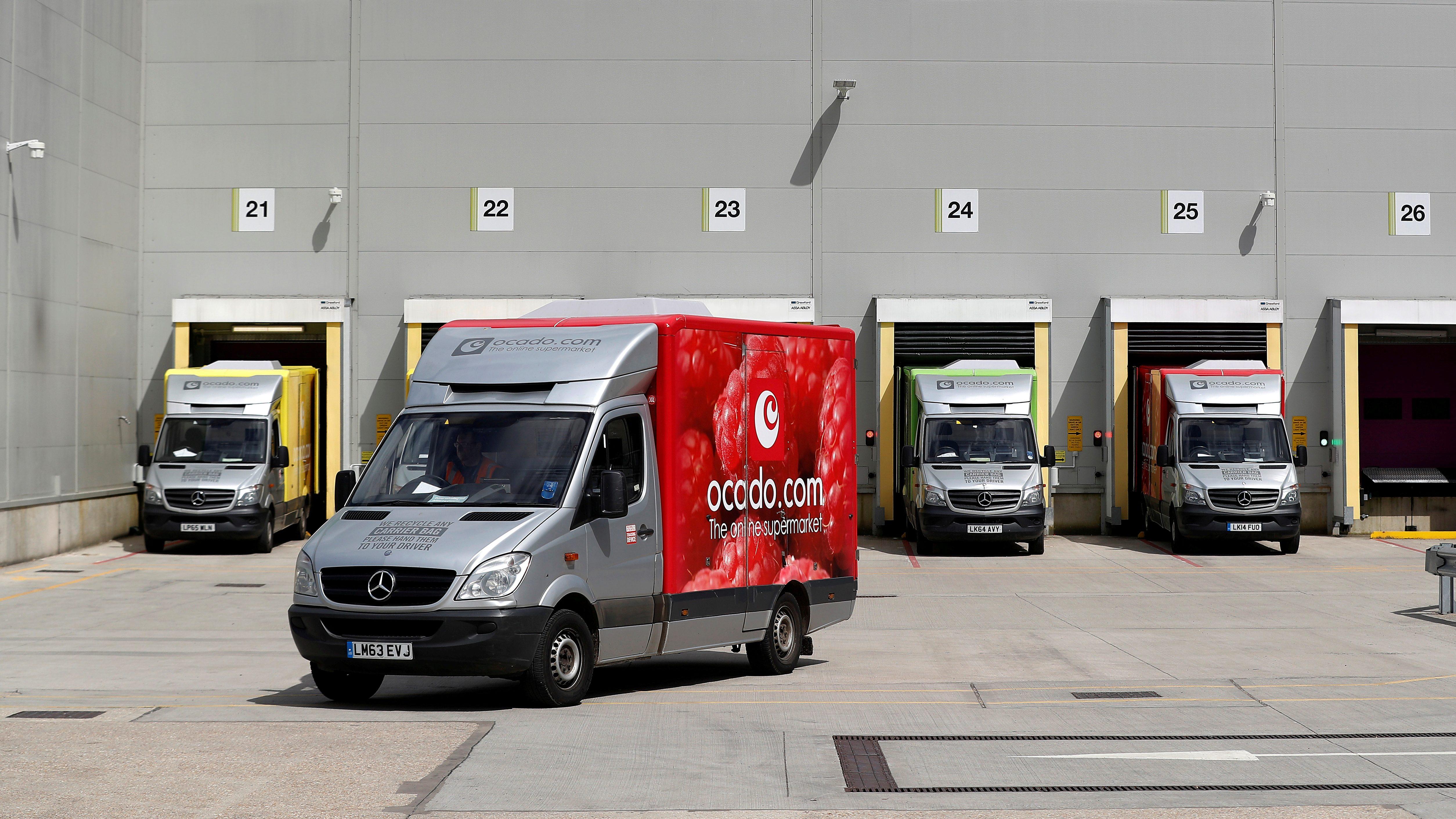 Ocado delivery trucks leave a facility.