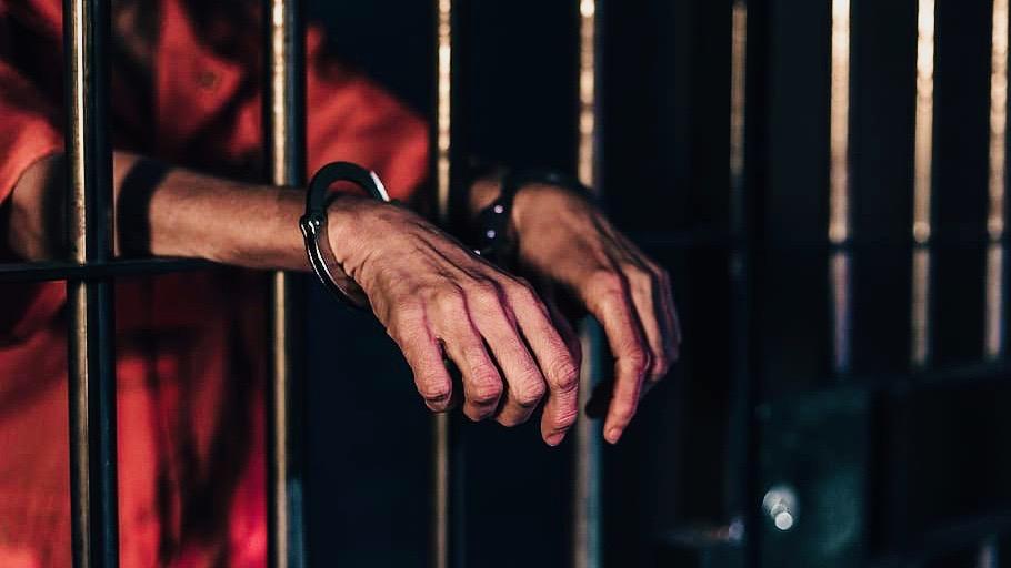 Man in handcuffs behind prison bars.