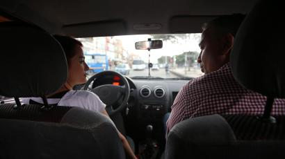 An Uber driver sits with a passenger