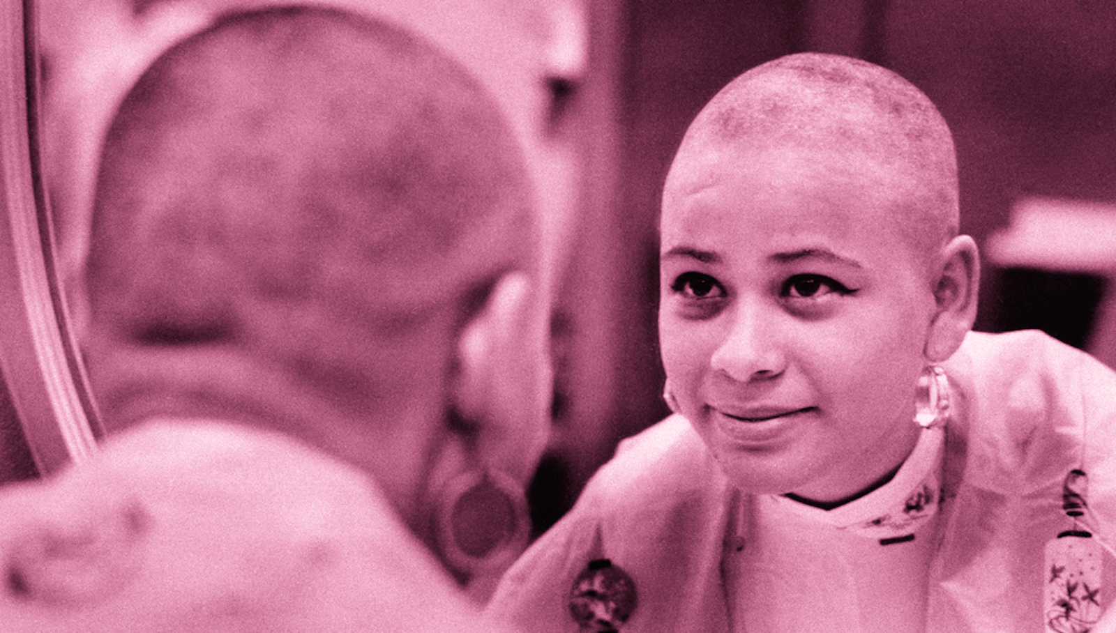 a woman with a shaved head looks in the mirror