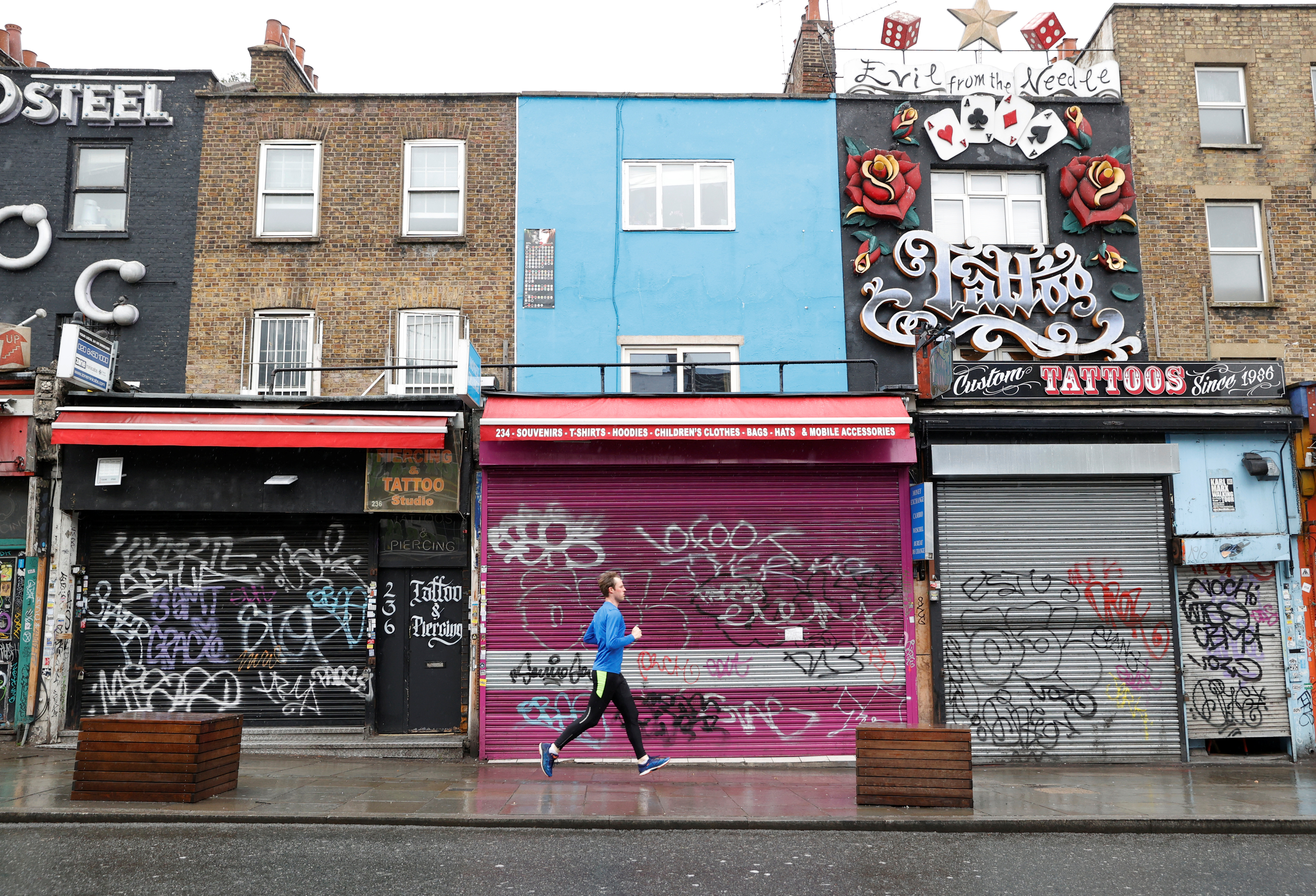 A man runs past closed shops in Camden, as the spread of the coronavirus disease (COVID-19) continues, London, Britain, April 28, 2020