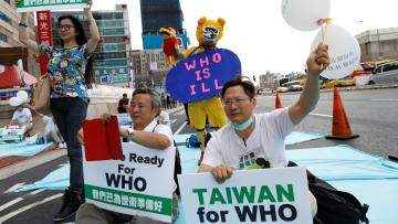 Protesters hold signs in favor of Taiwan becoming part of the WHO.
