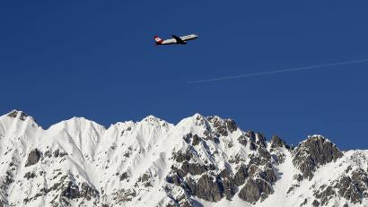 An Austrian Airlines plane takes off above the alps in Innsbruck, Austria.