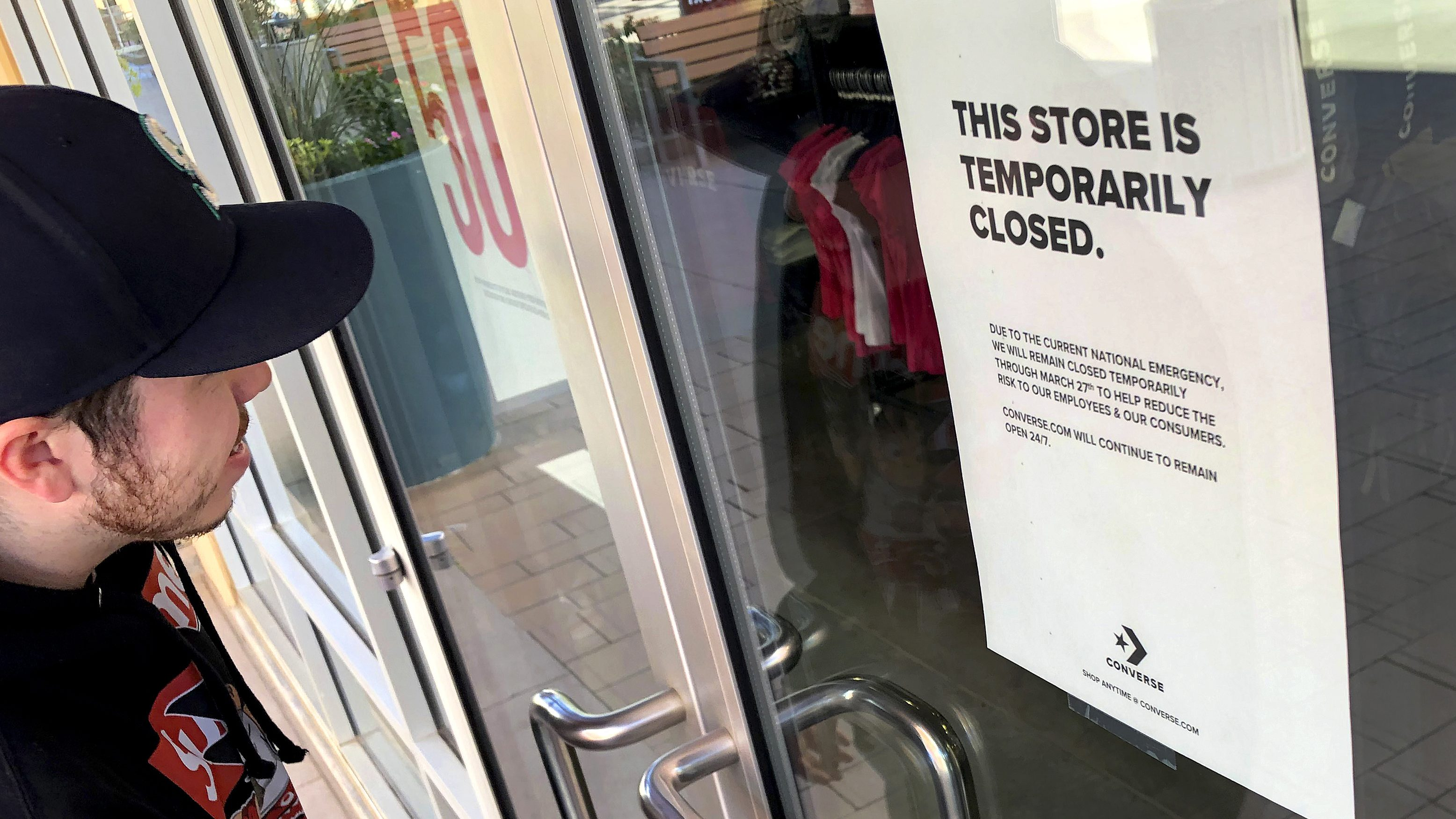 An employee enters a closed Converse shoe store Monday, March 15, 2020, in Phoenix