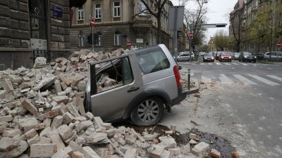 A car is crushed by falling debris after an earthquake in Zagreb, Croatia, Sunday, March 22, 2020. A strong earthquake shook Croatia and its capital on Sunday, causing widespread damage and panic.