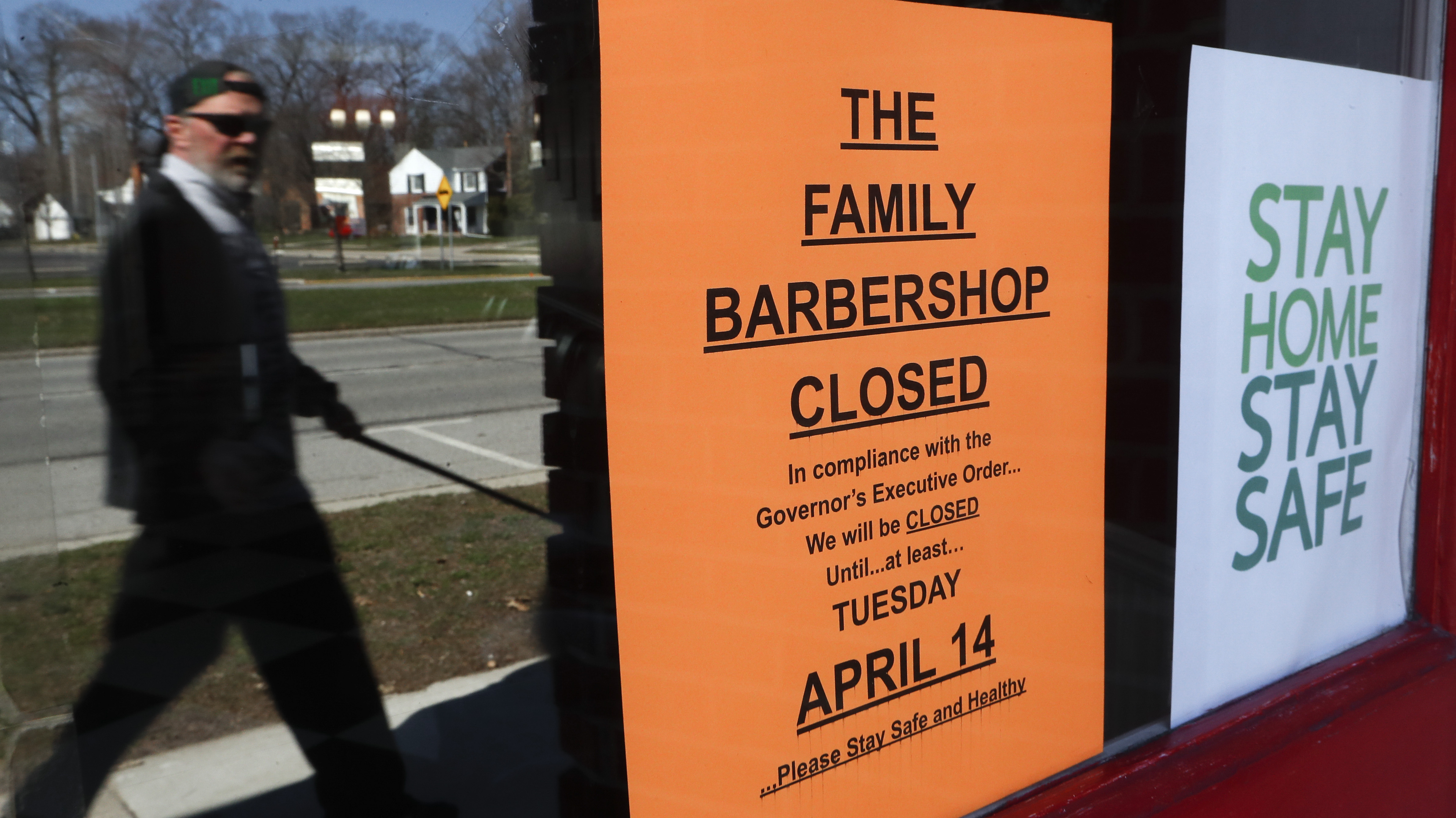 A pedestrian walks by The Family Barbershop, closed due to a Gov. Gretchen Whitmer executive order, in Grosse Pointe Woods, Mich., Thursday, April 2, 2020. The coronavirus COVID-19 outbreak has triggered a stunning collapse in the U.S. workforce with millions of people losing their jobs in the past two weeks and economists warn unemployment could reach levels not seen since the Depression, as the economic damage from the crisis piles up around the world.