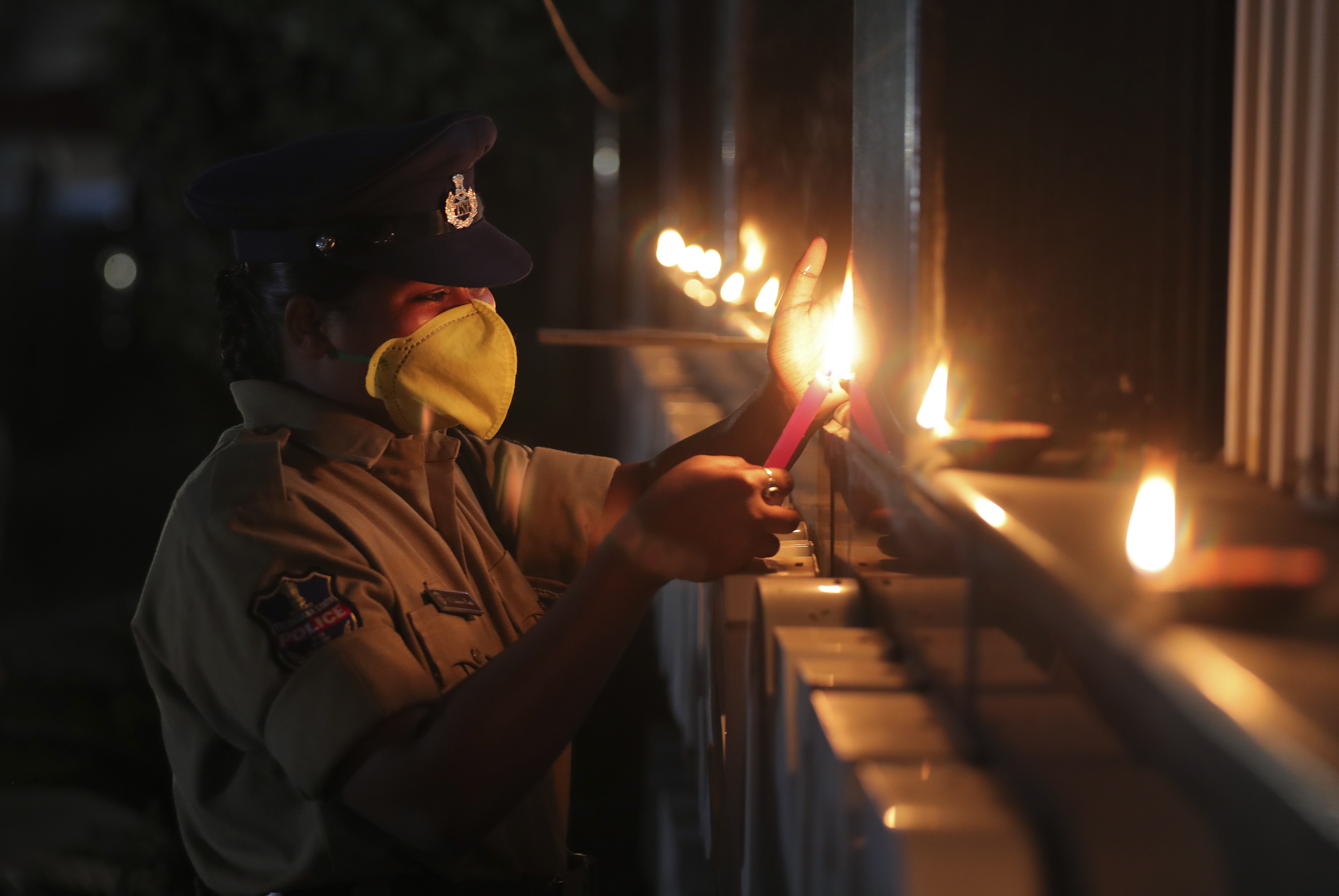 An Indian policewoman lights earthen lamps in Hyderabad.
