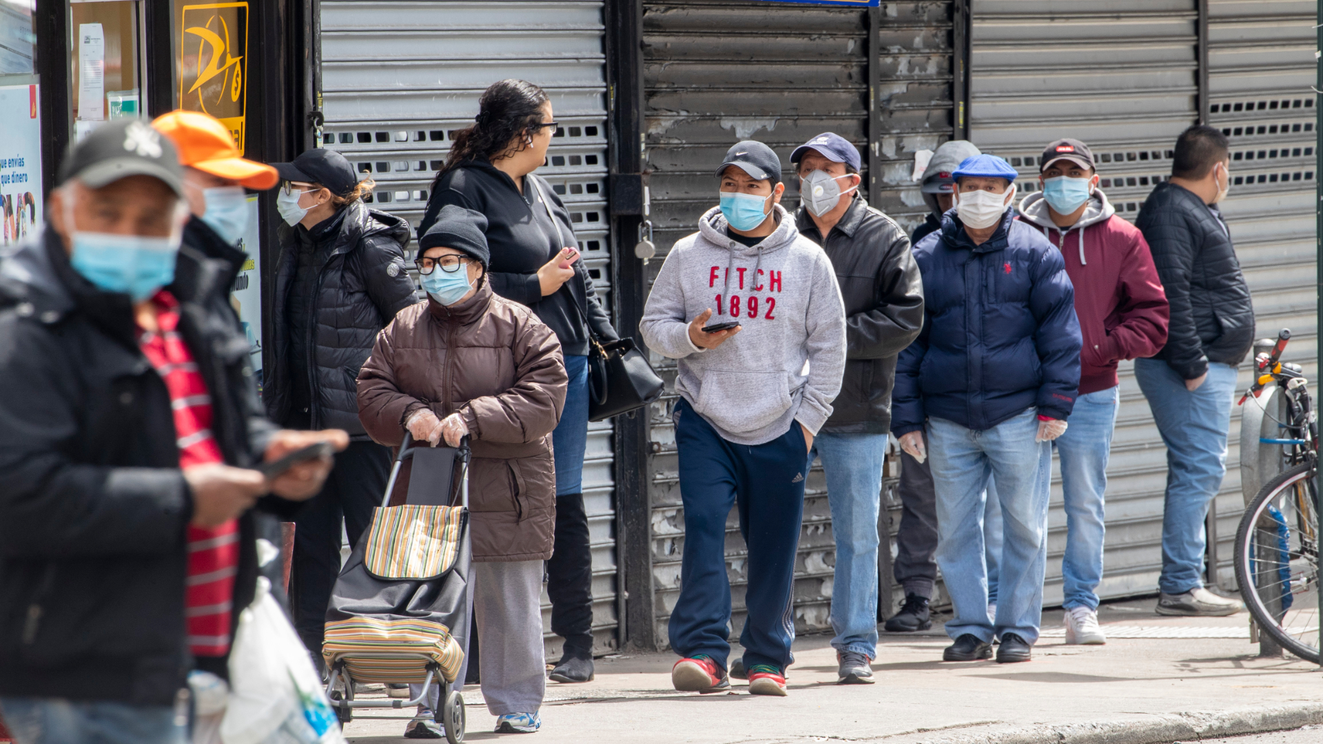 Line of people wearing face masks, waiting to enter a grocery store