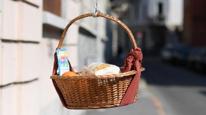 A basket of food hanging from an apartment building.