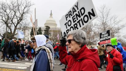 Anti-abortion activists march with signs past the US Capitol