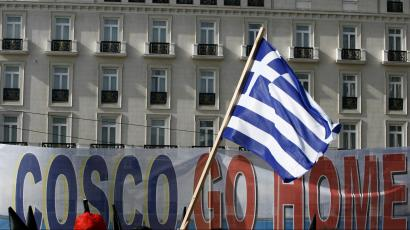 """Protesters raise a Greek flag in front of a banner that reads """"Cosco Go Home"""""""
