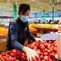 Wearing a mask and gloves, a worker re-stocks apples in an Asian grocery store