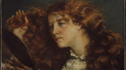 A red-haired woman brushes her hair while looking in the mirror in a painting by Gustave Courbet